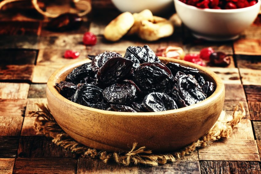 Dried sweet prunes or dark plums in bowl
