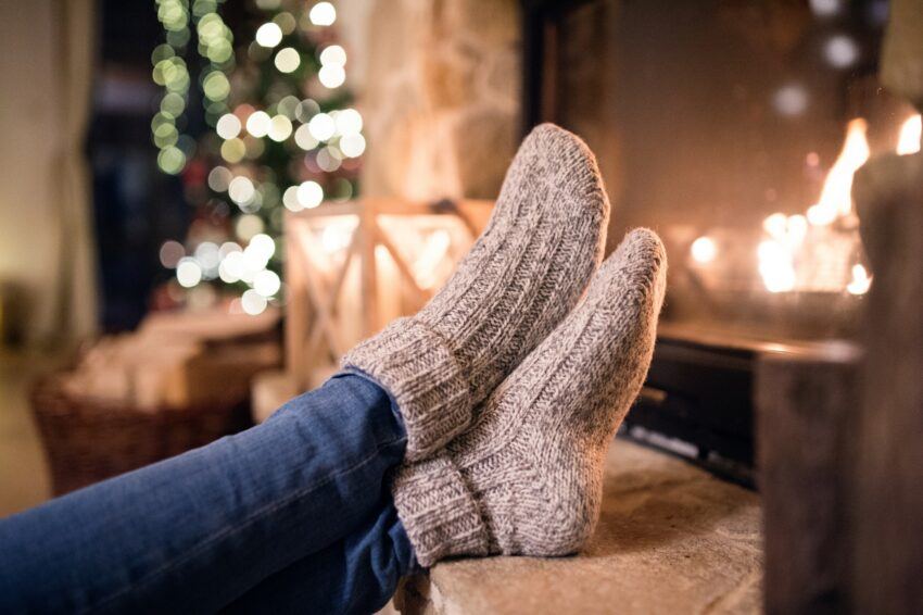 Feet of unrecognizable woman in socks by the Christmas fireplace.