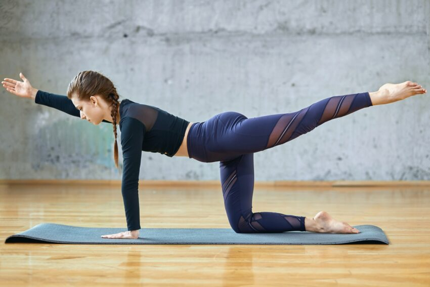 Fit woman stretching in hall
