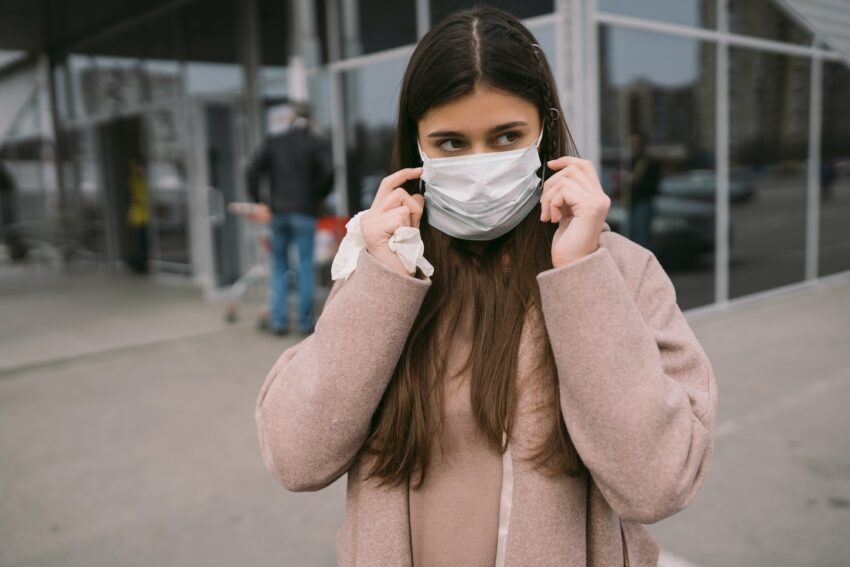 Woman puts on a protective medical mask